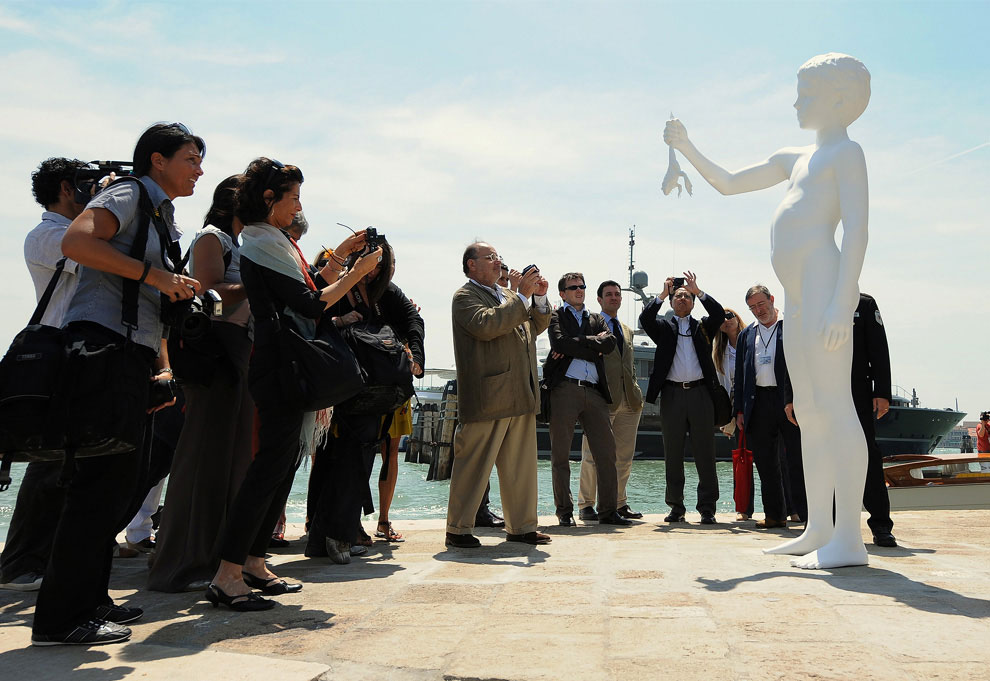 "Journalists take pictures of ""The Boy with the frog"" by US artist Charles ray in front of the Punta della Dogana in Venice during the opening of Francois Pinault's new museum on June 3, 2009. (ALBERTO PIZZOLI/AFP/Getty Images) #"